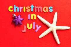 Noël de mots en juillet sur un fond rouge avec une étoile de mer et une babiole de forme d'étoile Photos stock