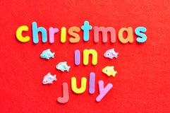 Noël de mots en juillet sur un fond rouge et des figurines de dauphins Image stock