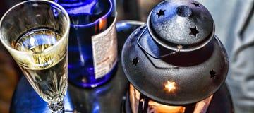 Noël de nouvelle année Champagne en verres et dans une bouteille, une lanterne de Noël avec une bougie brûlante sur la table de f Images libres de droits
