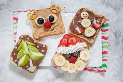 Noël drôle fait face à des pains grillés avec la banane, la fraise et la myrtille Photo stock