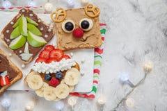Noël drôle fait face à des pains grillés avec la banane, la fraise et la myrtille Photos stock