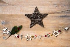 Noël en bois se tient le premier rôle avec l'étoile brune devant le backgr en bois Images stock