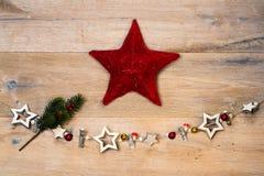 Noël en bois se tient le premier rôle avec l'étoile rouge devant le backgrou en bois Images libres de droits