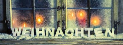 Noël en texte allemand : Décoration de fête de fenêtre avec des bougies Photo stock