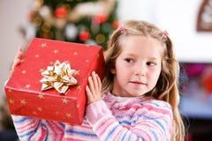 Noël : Essais de jeune fille pour deviner ce qui est en cadeau enveloppé Image stock