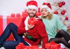 Noël est l'heure pour donner Les couples affectueux caressent le sourire tout en déballant des cadeaux avec le fond d'arbre de No images stock