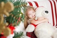Noël fait maison, fille étreignant un ours de nounours Photographie stock