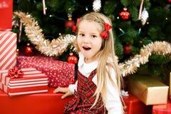 Noël : Fille accablée par la pile de cadeaux Photos stock