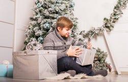 Noël - l'homme caucasien de sourire heureux ouvre le boîte-cadeau Photographie stock