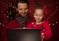 Noël - père et fille jouant le jeu sur l'ordinateur portable photo libre de droits