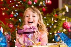 Noël - petite fille avec le présent de Noël Photographie stock libre de droits