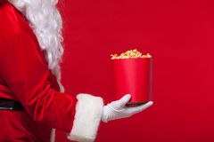 Noël Photo de main enfilée de gants de Santa Claus avec un seau rouge avec le maïs éclaté, sur un fond rouge Photos libres de droits