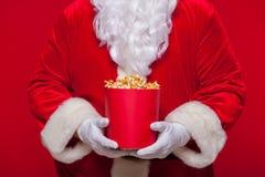 Noël Photo de main enfilée de gants de Santa Claus avec un seau rouge avec le maïs éclaté, sur un fond rouge Image libre de droits