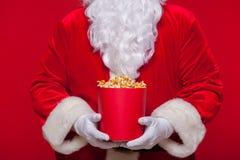 Noël Photo de main enfilée de gants de Santa Claus avec un seau rouge avec le maïs éclaté, sur un fond rouge Images stock