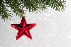 Noël rouge se tient le premier rôle sur l'arbre de Noël sur le fond de bokeh de scintillement Images libres de droits