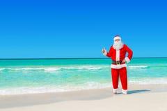 Noël Santa Claus à la plage tropicale manie maladroitement vers le haut du geste de main Photos libres de droits