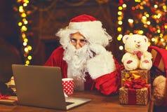 Noël Santa Claus avec la lettre de lecture d'ordinateur portable Images stock