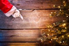 Noël Santa montrant l'espace vide de copie sur un fond en bois Photos stock