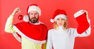 Noël stockant la tradition Couplez la chaussette de prise de costume de Santa de Noël et la boule d'ornement Concept de célébrati photographie stock libre de droits