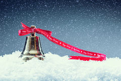Noël Temps de Noël Cloche de Noël avec le ruban rouge et le fond neigeux Texte de Noël heureux Photos libres de droits
