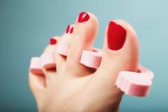 Nożny pedicure stosuje czerwonych toenails na błękicie Zdjęcie Stock