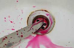 Nożowy ostrze z krwionośnym pluśnięciem na białej ceramicznej zlew łazience Obrazy Stock