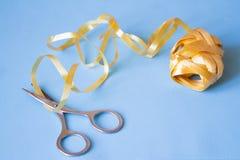 Nożyce cią żółtego faborek na błękitnym tle zdjęcie royalty free