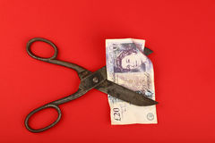 Nożyce cią Brytyjskiego funt nad czerwonym tłem Fotografia Stock