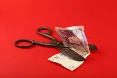 Nożyce cią Brytyjskiego funt nad czerwonym tłem Zdjęcie Stock