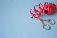 Nożyce cią czerwonego faborek na błękitnym tle fotografia stock