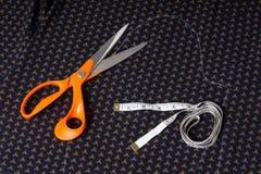 Nożyce dostosowywają i posuwają się wolno, centymetrowa taśma na tle błękitny Zdjęcie Royalty Free