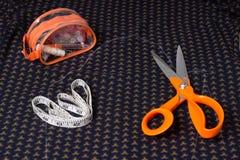 Nożyce dostosowywają i posuwają się wolno, centymetrowa taśma na tle błękitny Zdjęcia Royalty Free