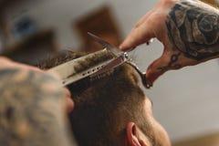 Nożyce i grępla w rękach fryzjer męski Obrazy Stock