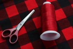Nożyce i zagrożenie na czerwonej tkaninie Fotografia Royalty Free