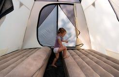 No acampamento, uma menina em saltos de uma barraca em colchões imagem de stock royalty free