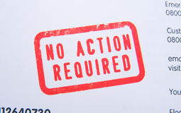 No action required stamp. A macro image of a red 'no action required' stamp in bold upper case text on an insurance renewal policy Royalty Free Stock Image