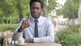 No, African Businessman Shaking Head To Reject while Sitting in Outdoor Cafe