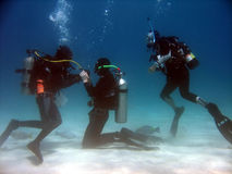 No air. A scuba student practicing taking air from the instructor while another student watches royalty free stock image