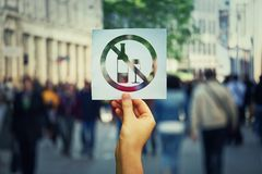 No alcohol. Hand holding a paper sheet with no alcohol sign over a crowded street background. Stop to drink symbol prohibited icon. Refuse to be dependent stock image