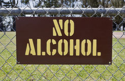 NO ALCOHOL Sign Attached to Park Fence. Yellow on brown NO ALCOHOL sign attached to public park fence Stock Photos