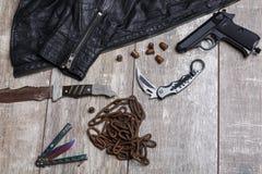 No assoalho há um revestimento, uma corrente, cartuchos, uma pistola e diversas facas imagens de stock royalty free