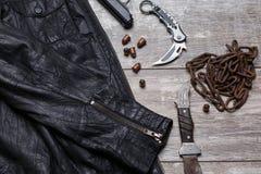 No assoalho são um casaco de cabedal, uma corrente, os cartuchos, uma pistola e duas facas fotografia de stock