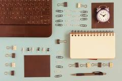No azul um fundo é um caderno, no canto um portátil Os botões de Staples e do papel são arranjados ordenadamente nas fileiras A Imagem de Stock Royalty Free