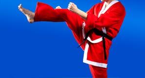 No azul um fundo bate o karateka que retrocede em um terno de Santa Claus Foto de Stock