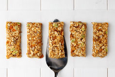 No bake energy granola bars on white wooden table. No bake energy granola bars on white wooden table with spatula. Top view Stock Photography