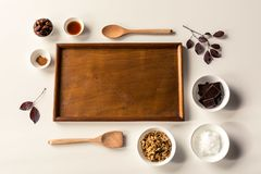 No Bake Raw Food Chocolate Cheesecake ingredients. Some ingredients used to make a paleo/vegan style chocolate cheesecake with wooden spoons and tray with leaves Stock Images
