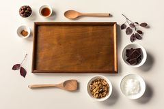 No Bake Raw Food Chocolate Cheesecake ingredients. Some ingredients used to make a paleo/vegan style chocolate cheesecake with wooden spoons and tray with leaves Stock Photography