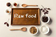 No Bake Raw Food Chocolate Cheesecake ingredients. Some ingredients used to make a paleo/vegan style chocolate cheesecake with wooden spoons and tray with leaves Stock Image