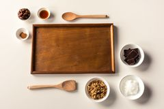No Bake Raw Food Chocolate Cheesecake ingredients. Some ingredients used to make a paleo/vegan style chocolate cheesecake with wooden spoons and tray with leaves Royalty Free Stock Images