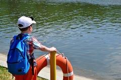 No banco do rio é um menino e olha a água foto de stock